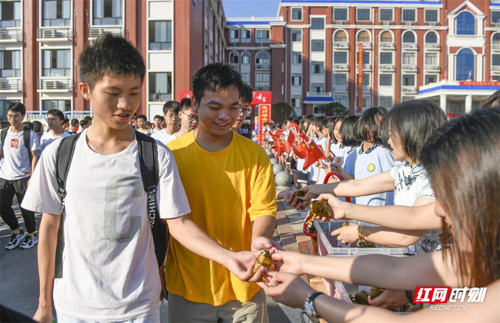 """6月7日,湖南省道县道州玉潭学校,老师给考生分发粽子,祝考生""""高中""""。"""