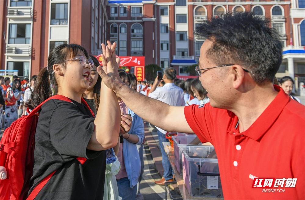 6月7日,湖南省道县道州玉潭学校,老师与考生击掌,为考生鼓劲加油。